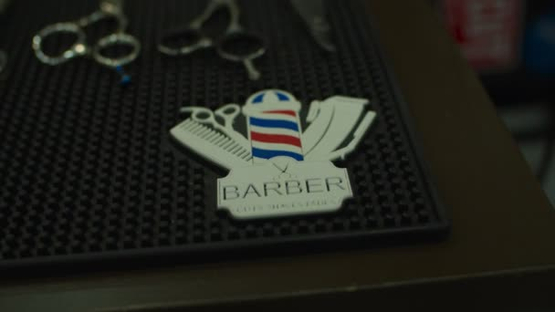 Barbershop logo on rubber mat with barber tools like scissors laying on.