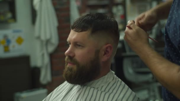 Mans hajvágás fodrász ollóval és fésülködni fodrászati logó mögött lassított felvételen. Férfi kéz, hogy férfi frizura szalonban.
