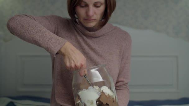weinende junge brünette Frau, die Vanille und Schokoladeneimer in Händen hält und auf dem Bett sitzt. aufgebrachte Frauen, die Süßigkeiten essen. Dia-Ansicht