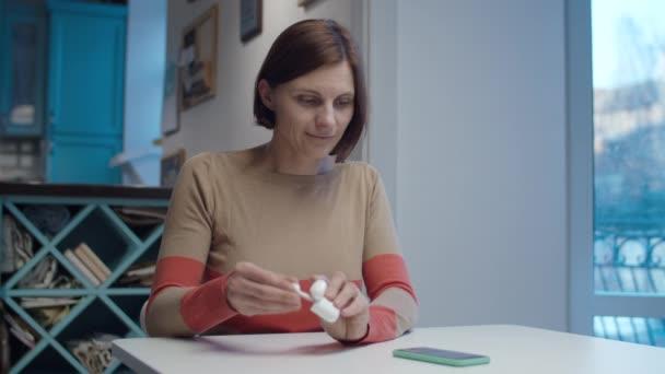 Mladá brunetka si bere bezdrátová sluchátka k uším sedícím u stolu. Žena se směje a hledá smartphone.