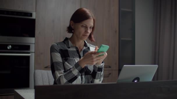 Freiberuflerin tippt auf Smartphone am Küchentisch mit Laptop. Frauen arbeiten zu Hause mit Gadgets.