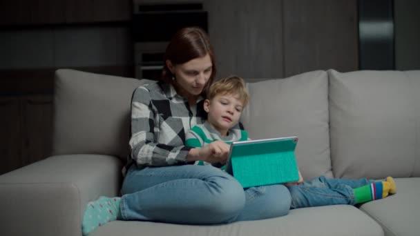 Matka objímající syna s tabletovým počítačem sedícím na útulné pohovce. Žena pomáhá chlapec s gadget.
