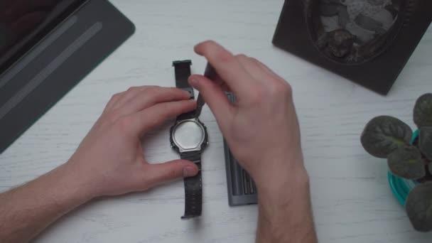 Muž ruce opravy a čištění hodinek podle malého přenosného šroubováku na bílém dřevěném stole, horní pohled.