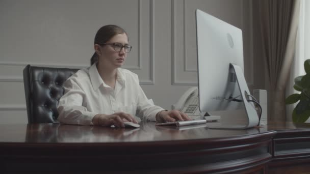 Mladá obchodnice pracující za stolem s monitorem, který sedí v křesle v kanceláři. Šéfka chce kávu. Šálek kávy se objeví na stole.
