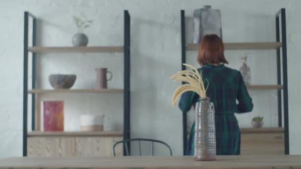 Mladá třicátnice bere vázy a hrnce z polic a dává je na dřevěný stůl. Minimalistické interiérové apartmány. Žena obdivuje vnitřní předměty.