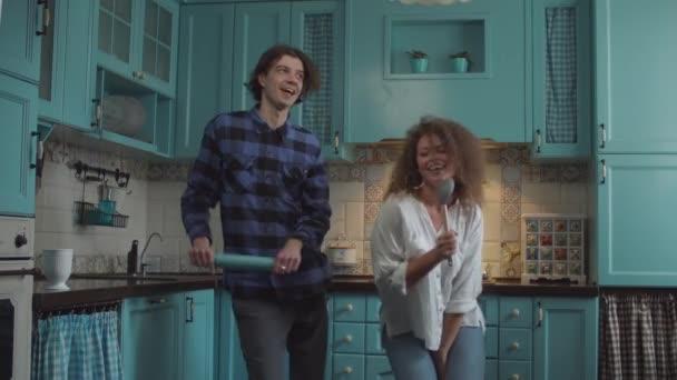 Fiatal boldog 20-as évek pár táncol alkalmi ruhát konyhai eszközök a kezében a hangulatos kék konyha. Férfi és nő szórakozás-val sodrófa és lapát otthon konyha