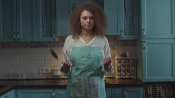 Verwirrte junge lockige 20er-Jahre-Frau mit Küchenutensilien in den Händen, zögernd den Kopf schüttelnd. Frau weiß nicht, wie zu kochen und trow weg Schaufel und Schöpfkelle.