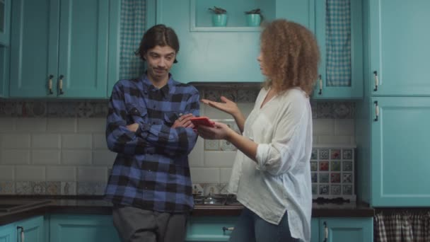 Mladý dvacetiletý pár se hádá doma na modré kuchyni, přítelkyně ukazuje mobil a křičí obviňujícího přítele. Rodinný konflikt žárlivosti.