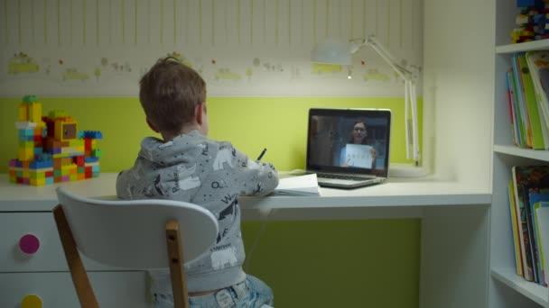 Vorschulkind macht Online-Hausaufgaben mit Lehrerin auf Laptop-Bildschirm. Kind holt Lehrbuch aus dem Regal, sitzt am Schreibtisch und lernt online im Kinderzimmer zu Hause.