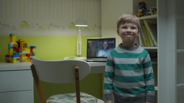 Preschooler boy smiling standing at children room at home with online lesson on laptop behind. E-studying happy kid looking at camera.