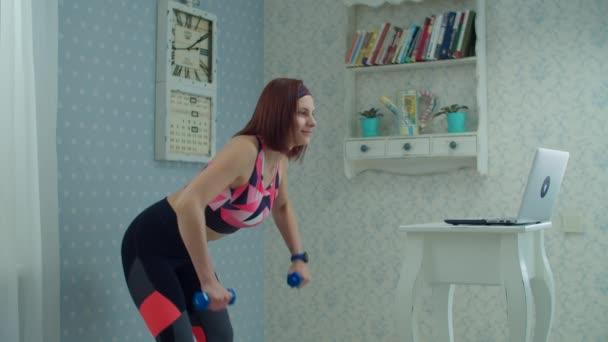 30s žena ve sportovním oblečení stojící před notebookem a dělat biceps a triceps cvičení s činkami doma ve zpomaleném filmu.