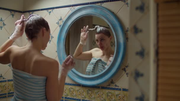 30s woman in towel dyeing her hair at home and dancing in mirror reflection. Brunette woman with dye on hair dancing in bathroom in slow motion.