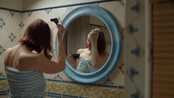 30s woman in towel dyeing her hair at home with brush and dye in mirror reflection. Brunette woman with naked shoulders in bathroom at home making spa.