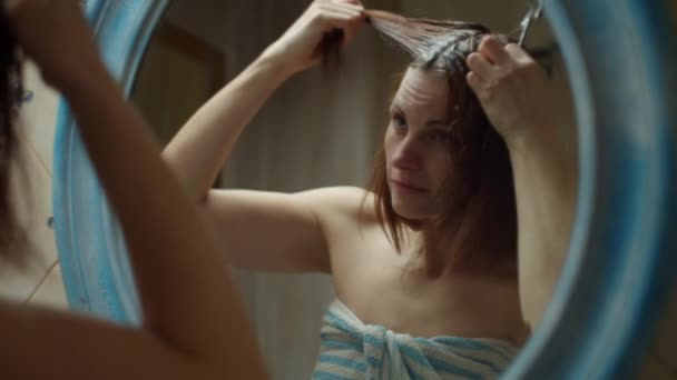 30s woman in towel dyeing her hair at home with brush and dye in mirror reflection. Brunette woman with naked shoulders in bathroom at home making spa. Close up