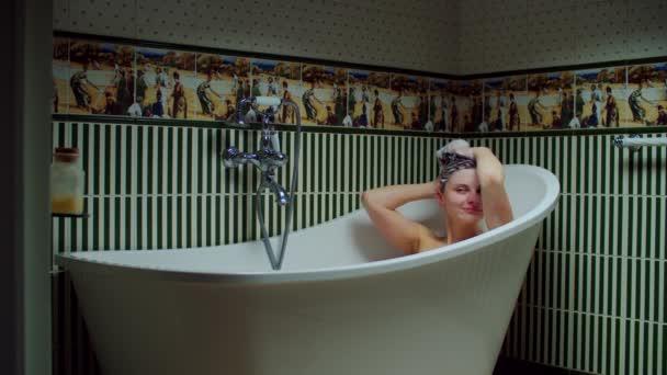 Mladá třicátnice si doma myje vlasy ve vaně pěnou v zelené koupelně. Žena dělá procedury koupele.
