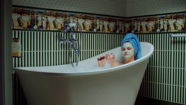 Mladá třicátnice používá pilník na nehty ve vaně s pěnou v zelené koupelně doma. Žena se zelenou kosmetickou maskou na obličeji tvorby nehtů procedury ve vaně.