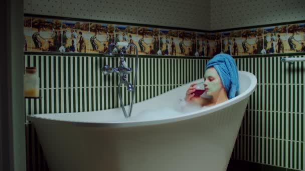 Mladá třicátnice pije červené víno ve vaně s pěnou v zelené koupelně doma. Žena se zelenou kosmetickou maskou na obličeji relaxační ve vaně.