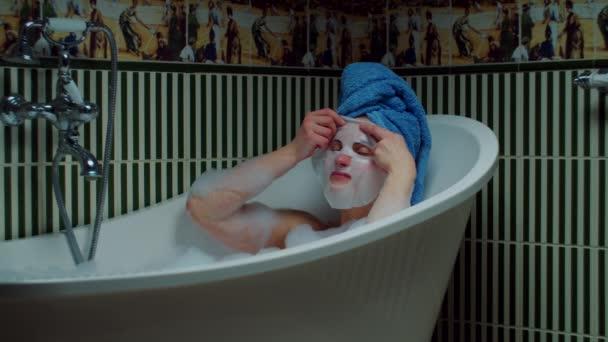 A 30-as éveiben járó fiatal nő kozmetikai maszkot visel, ahogy otthon ül a fürdőkádban habbal a zöld fürdőben. Egy nő kék törölközővel a fején, aki a fürdőkádban pihen. Otthoni spa koncepció. Közelről.