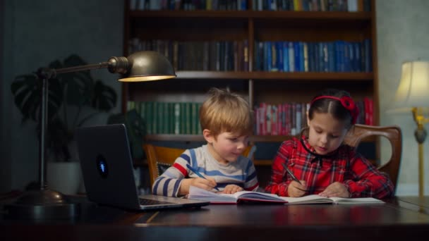 Two preschool kids making online homework at home. Siblings writing with pens in notebooks together looking at laptop. Online home education process.