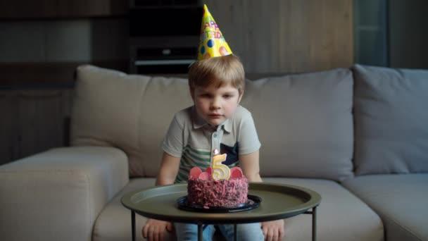 Školák v narozeninovém klobouku sfouknul svíčku s číslem 5 na čokoládovém dortu doma. Kid slaví 5 let doma sám.