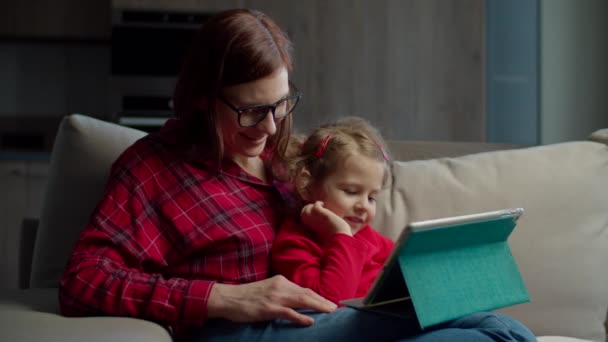 Mladé 30s matka v brýlích s malou holčičkou pomocí tabletu počítače pro vzdělávání on-line sedí na gauči doma. Rodina používající společně online aplikaci.