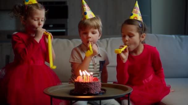Tři šťastné děti v narozeninových kloboucích si doma troubí na narozeninové fajfky. Bratři a sestry slaví narozeniny čokoládovým dort se svíčkou sedí na gauči v obývacím pokoji.