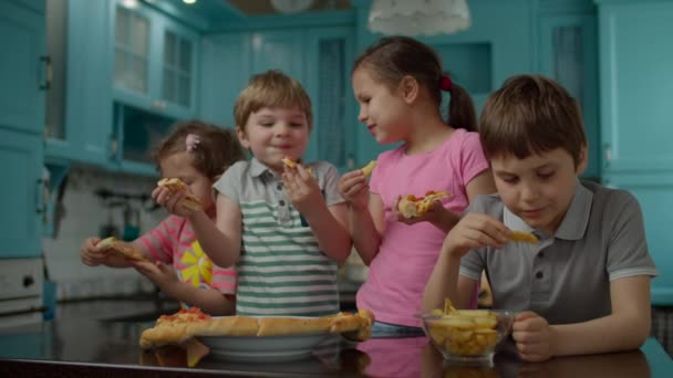Group of four mixed age kids eating homemade pizza and potatoes standing on blue kitchen at home. Two boys and two girls enjoy eating pizza with hands.