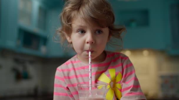 Nettes kleines Mädchen in rosa T-Shirt trinkt Beeren-Smoothie mit Papierstroh zu Hause blaue Küche. Kinder genießen hausgemachten Milchshake. Nahaufnahme
