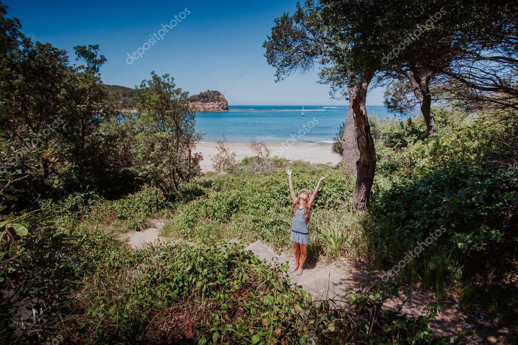 Woman arriving to the beach after hiking in the forest.