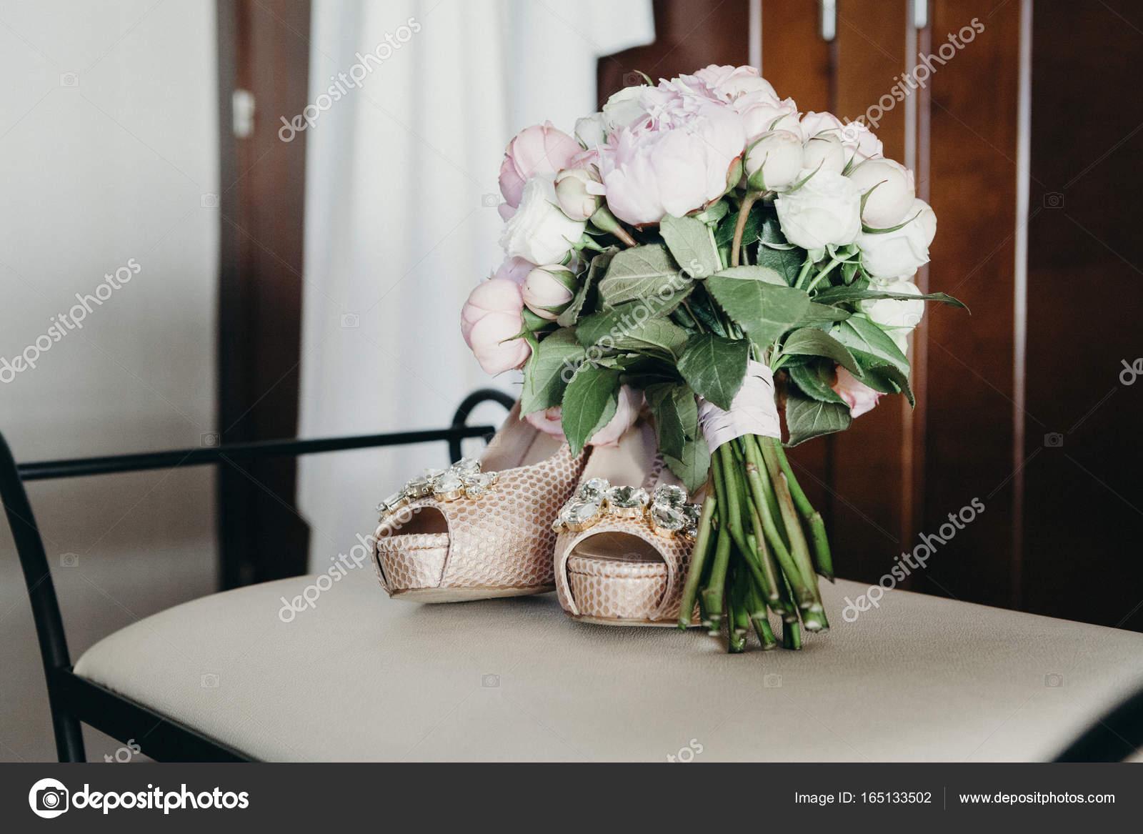 11d9bebe0df2 Κοντινό πλάνο του παπούτσια γάμου και νυφική ανθοδέσμη σε μια καρέκλα —  Εικόνα από ...