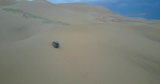car drives to the top of a sand dune in the Gobi desert in Mongolia