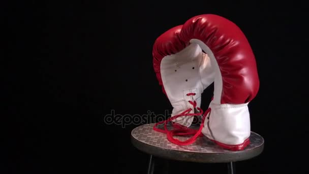 Rote Boxhandschuhe rotieren auf rundem Hocker.