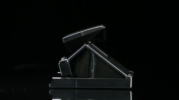 Polaroid camera rotating on reflective surface.