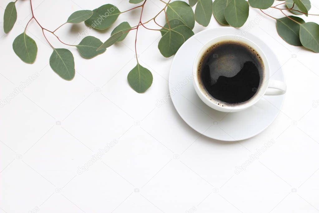 Floral composition made of green eucalyptus leaves and branches on white wooden background with cup of coffee. Feminine office desk, styled stock image, flat lay, top view with empty space.