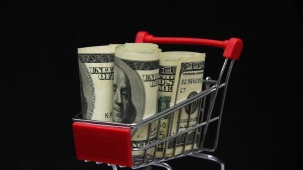 Hromada dolarů rotujících v vozíku v supermarketu. Peníze v nákupním vozíku. Online nakupování. Obchod.