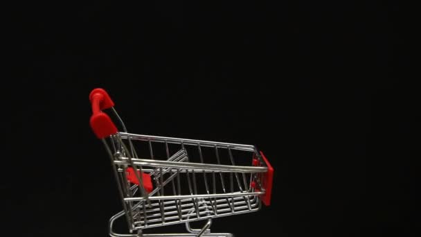 Rotating miniature metal empty shopping cart on black background. Shopping, sales theme