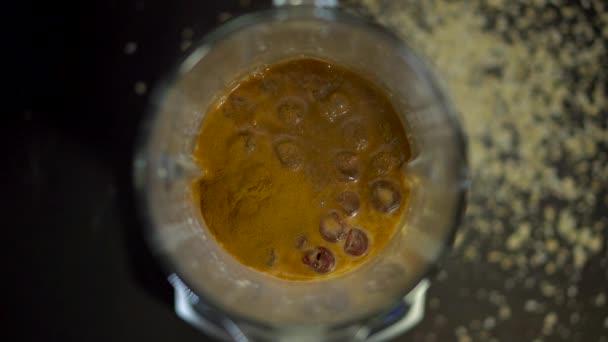 Víko mixéru bylo umístěno na hnědý nápoj se skořicovým kořením. Káva s mlékem, kakao, Cola se otáčí v mixéru.