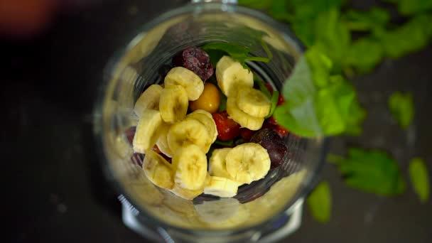 Gefrorene Erdbeeren fallen auf Kirschen, im Kreis geschnittene Bananen, rote Preiselbeeren, schwarze Johannisbeeren im Mixer auf grünen Spinatblättern. Zutaten zum Kochen. Smoothies im Mixer. Gesunde Speisen und Getränke aus Gemüse, Obst und Gemüse