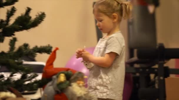 Ein kleines Mädchen hängt ein Reh an den Baum. Rudolph zu Weihnachten. Ein Kind macht Wohnaccessoires für das neue Jahr.