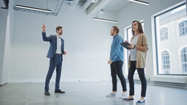 Realitní agent ukazující mladým mužům a ženám nový prázdný kancelářský prostor. Podnikatelé setkat makléř s tabletou a diskutovat o zařízení, které si přejí koupit nebo pronajmout.