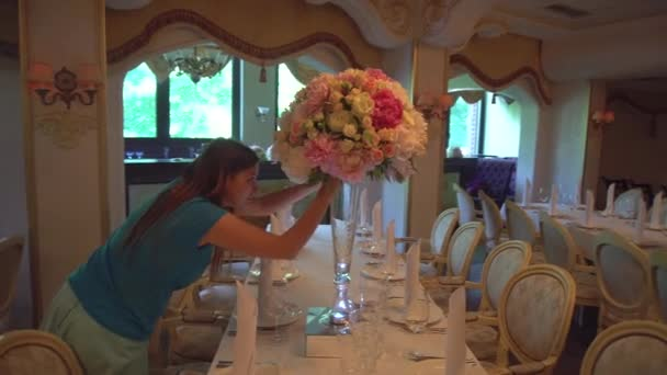 Young Woman With Flowers Decorates the Table