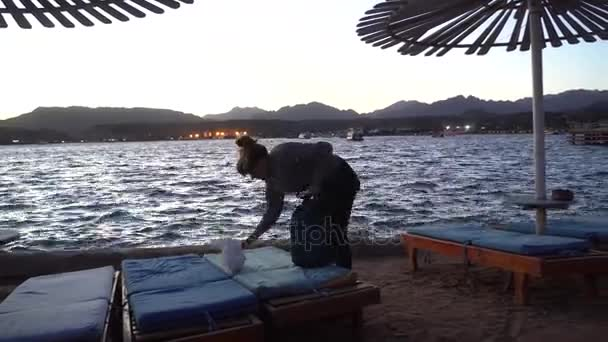 Female Takes Away Things From Beach Chair at Dusk