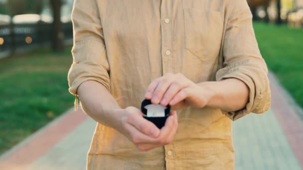 A young man holding a box with wedding ring 4k