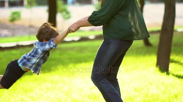 Šťastný matka a syn baví venku. Směje se maminka s malým synem společně užívat přírody. Na zádech, létání. Radostné rodinné. Koncept svobody. Letní prázdniny, dovolená. Zpomalený pohyb