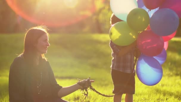 mother and child with balloons playing on the beach at the sunset time. Concept of friendly family.Slow motion. Close up