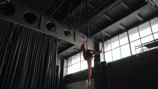 Young adult athlete female using hoop, making flexibility twine exercise