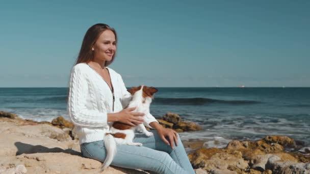 Mladá dospělá žena tráví den na pláži s malým psem
