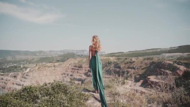 Mladá dospělá dáma stojí venku v půvabných zelených šatech
