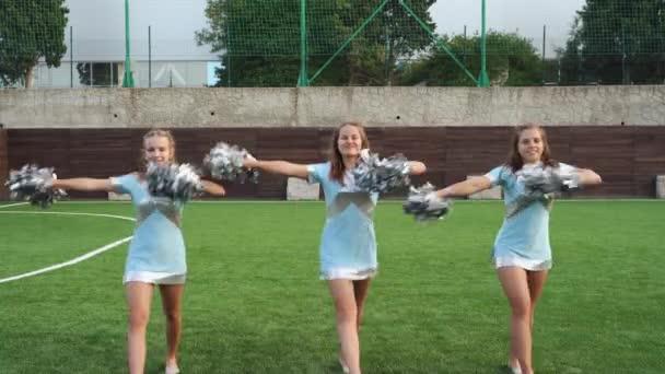 Teenage girls in cheerleaders uniform with pom poms support sport team