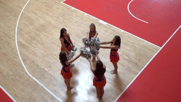 Proud cheer leaders girls in uniform with pom poms support high school sport team